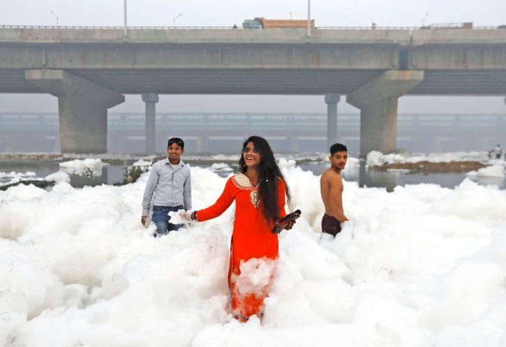 Devotees praying in white toxic foam in the Yamuna river